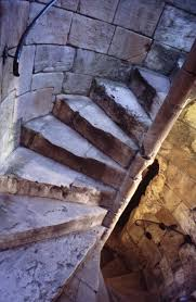 Spiral staircase in an old stone tower interior winding their way upwards
