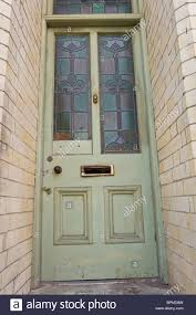 victorian paneled with stained glass scruffy green painted front door of brick built house in llandrindod wells mid wales uk