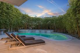 at a lavish home in los angeles the kidney shaped swimming pool is shaded