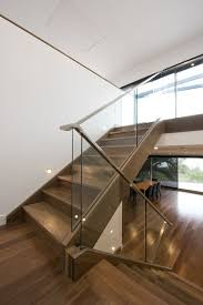 modern staircase with a glass barade and wooden handrails for a contrast
