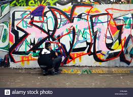 graffiti artist at work spray can painting a wall leake street london se1 on graffiti artist wall street with graffiti artist at work spray can painting a wall leake street