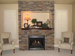 interior tall grey stone fireplace with black metal fire box and brown wooden mantel between double white wooden windows plus white sofa on grey rugs