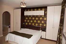 bedroom furniture designers. ivory shaker bedroom wrapped in dark walnut panelling furniture designers l