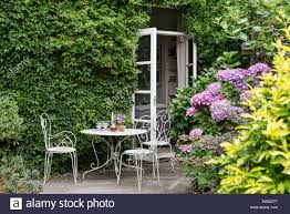 white wrought iron furniture. french windows leading out to garden with white wrought iron furniture rhododendrons and jasmin u