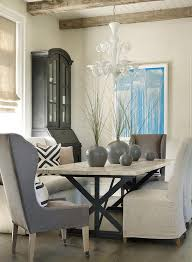 lovely dining room features an iron x based dining table lined with wingback dining room chairs