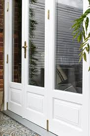 timber white bifold door with brass hinges and lock