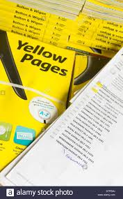 bundles of yellow pages business telephone directory for the bolton wigan area of england