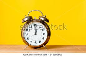 photo of beautiful alarm clock on the wonderful yellow studio background u3