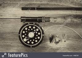 vintage concept of an antique fly fishing reel and rod on rustic wood layout in