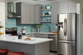 corner view of condo kitchen with gray slab door cabinets ceiling high aqua glass mosaic