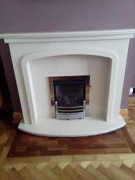 cream colour fire surround and metal trim curved hearth and 2 down lights