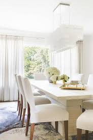 alyssa rosenheck white rectangular tiered chandelier with modern white dining table