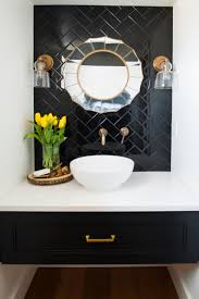 powder room featuring a black tile wall art deco mirror and white bowl sink