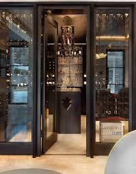 black framed glass doors whose sleek design lead into the dark cellar perfectly the black walls floors and ceiling create a darkly glamorous feel