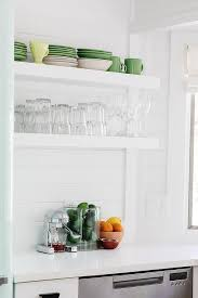 small cottage kitchen with tongue and groove wall backsplash white quartz countertops and white shelves bring a clean airy feel to the kitchen allowing