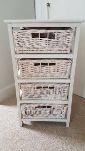 white washed storage unit with baskets