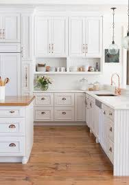 amazing kitchen features white raised panel cabinets adorned with copper hardware paired with white marble countertops