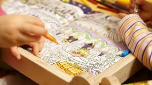 children drawing in a coloring colouring book close up closeup shot of two