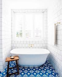 blue patterned bathroom floor tiles wooden side table white free standing bathtuub white subway tile bathroom wall white towel