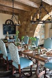 dining room blue padded dining chairs gather around an century table curved trestle base and nature simperfections a stone archway divides the e