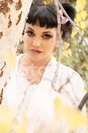 premium stock photo of seriös kvinna i docka makeup bakom defocused björk