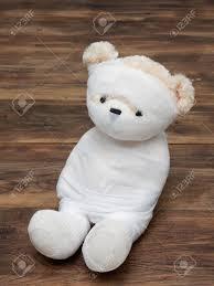 portrait of cute mummy teddy bear doll bind with white gauze or bandage on dark wooden