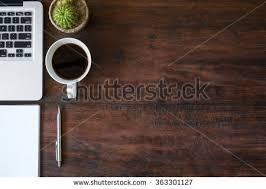 office wood table. wood office desk table with laptop a cup of coffee and supplies top view e