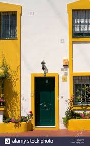 black door on white spanish house with black door and yellow frames
