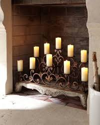 lovely wrought iron fireplace candelabra with bricked background for home decoration ideas