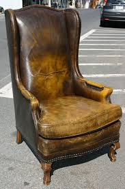 a nicely distressed and with good patina leather wing chair leather in a burnt caramel