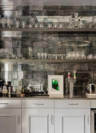 gray wet bar with antiqued mirror subway tile backsplash