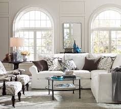 cotton sectional sofa in ivory round tempered glass coffee table grey polyester area rug metropolitan contemporary mirror in clear glasses table lamp with