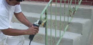 using a rotary wire bursh attachment to remove rust on railings