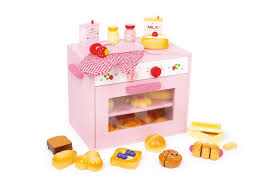 pink wooden toy oven and toy baking set with wooden cut and play toy food and lots of other toy kitchen accessories