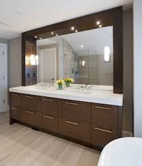 dark brown wooden bathroom vanity with white top and large mirror on