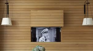 By placing the television behind a panel within the wood wall, it allows  the TV to be on show when needed, and completely hidden away without the  use of a ...