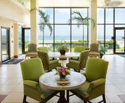 lobby with circular tables green sofa chairs large window panels with ocean view