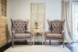 french sitting room features a pair of gray tufted wingback chairs flanking a round cream french accent table placed in front of a grey french art panel