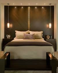 Master bed features a dark walnut headboard wall bisected by glass tile and  matched with flanking
