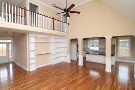 from this angle see the built in bookcase wall and second story overlook the two story foyer leads into the living room
