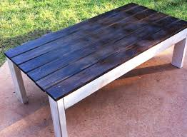 outdoor coffee table with wood stained top and white distressed base