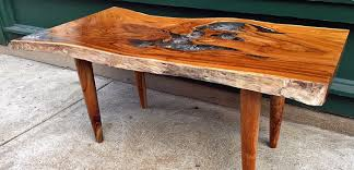 A rectangular coffee table made from reclaimed old growth teak tree slab  and clear resin on