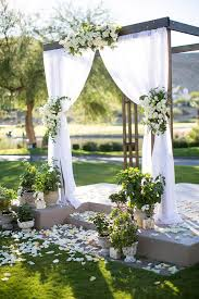 Romantic outdoor wedding altar with greenery and cream flowers