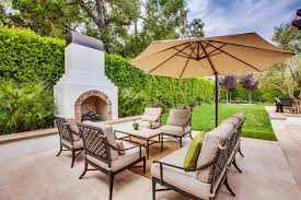 this spanish style outdoor fireplace provides the perfect place to cozy up to on a