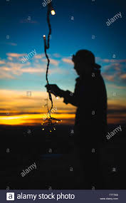 Fairy Lights Silhouette Silhouette Man Holding Fairy Lights While Standing On Field