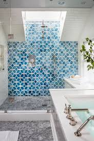 blue patterned tile accent wall in spacious glass door shower with white subway tile walls and gray marble flooring