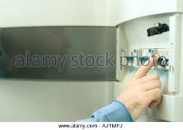 domestic fuse box close up trip switches circuit breakers man switching fuse in fuse box close up of hand stock photo