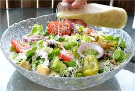 copycat olive garden salad dressing being poured over a large glass bowl filled with olive garden