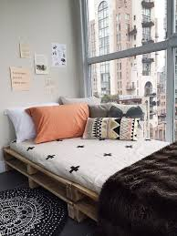 pallet bed facing a glass wall