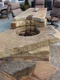 this custom bo table and fire pit crafted from natural stone slab with wood and steel accents make cool weather dining and entertaining more